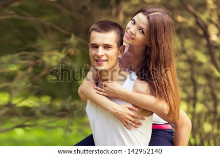 outdoors portrait happy couple. guy and girl on park. piggyback - stock photo