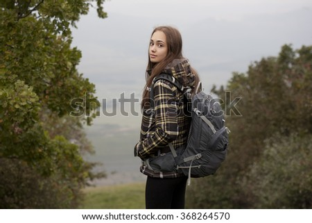 Outdoors portrait of a gorgeous young brunette woman hiking in nature.