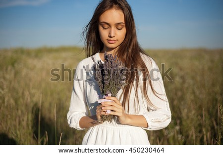 Outdoors portrait of a gorgeous young brunette woman holding lavender flowers.