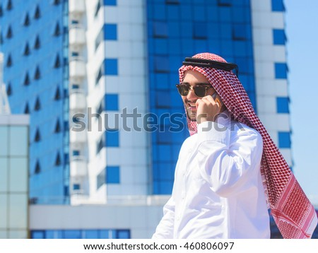 Outdoors portrait of a handsome arabian man talking on a cell phone