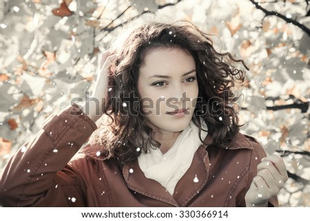 Outdoors portrait of a young beautiful woman with falling snow - stock photo