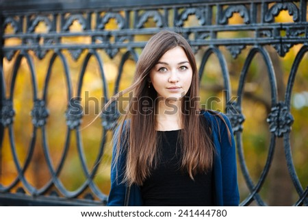 Outdoors portrait of a young cute woman with long hair against an iron fence - stock photo