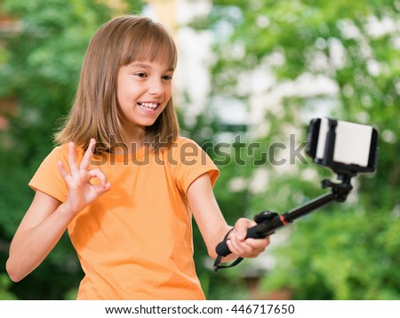 Outdoors portrait of beautiful little girl taking a selfie at the park. Child showing ok sign gesture. - stock photo