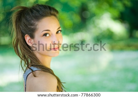 Outdoors portrait of beautiful young brunette girl. - stock photo