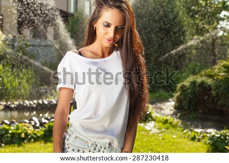 Outdoors portrait of beautiful young brunette girl in white silk shirt posing in summer garden.