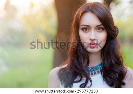 Outdoors portrait of beautiful young brunette woman looking at camera.
