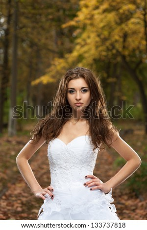 outdoors portrait of beautiful young caucasian brunette woman in white wedding dress over green foliage on background