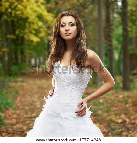 outdoors portrait of beautiful young caucasian brunette woman in white wedding dress over green foliage on background - stock photo
