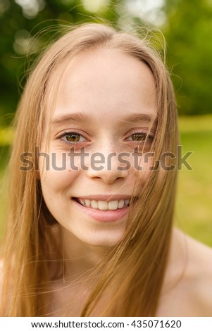 Outdoors portrait of beautiful young girl looking at you.
