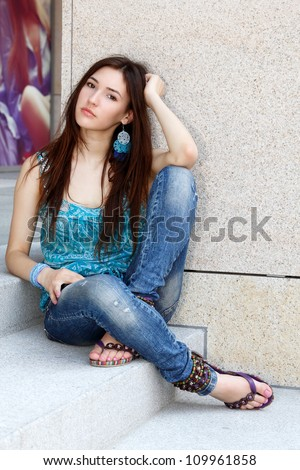 Outdoors portrait of beautiful young sad teen girl sitting on stairs - stock photo