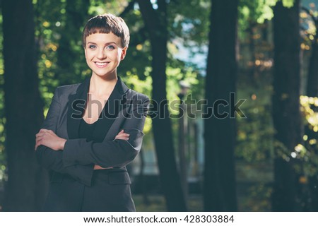 Outdoors portrait of confident attractive caucasian smiling young woman in formal wear keeping arms crossed and looking at camera at the park - stock photo