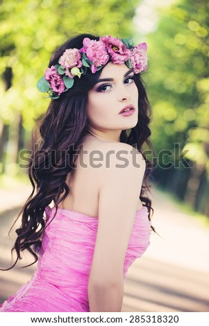 Outdoors Portrait of Fashion Woman. Beauty Summer Girl with Flowers on Sunny Greenery Background - stock photo