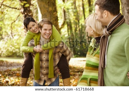 Outdoors portrait of happy young friends having fun in autumn park.?