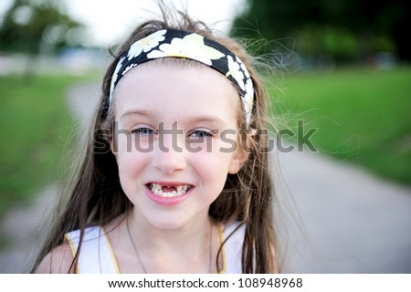 Outdoors portrait of little girl who lost her milk teeth