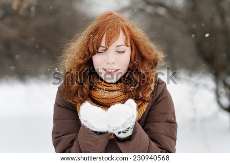 Outdoors portrait of young beautiful woman having fun in winter  - stock photo