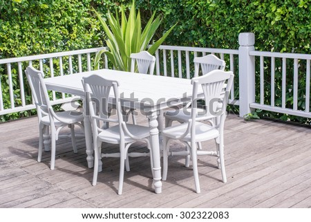 Outdoors seating on new remodeled wooden deck. with trees in background