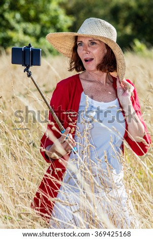 outdoors selfie - gorgeous 50s woman making a self-portrait on mobile phone on stick in the middle of a high dry grass,summer daylight - stock photo