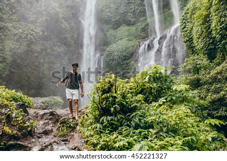 Outdoors shot of young man walking along mountain trail. Male hiker hiking in forest with waterfall in background.