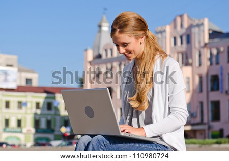 outdoors shot of young woman with laptop - stock photo