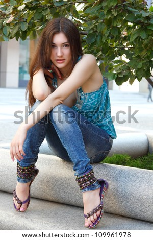 Outdoors street portrait of beautiful young brunette girl near tree - stock photo