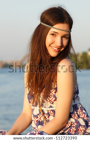 Outdoors summer portrait of beautiful young teen girl on the river bank - stock photo