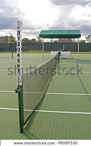 Outdoors tennis court and close up of net on a sunny and cloudy day - stock photo