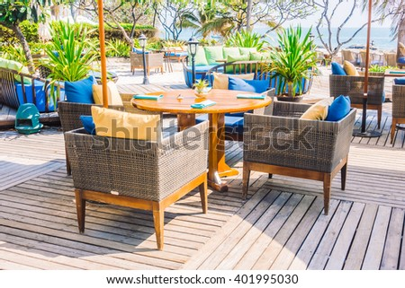 Outdoot patio with pillow on sofa and chair on the beach and sea - Vintage Light Filter