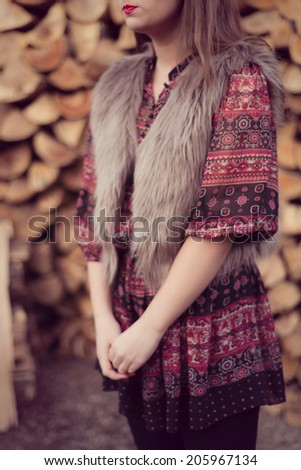 Outfit details of Fashion beauty posing in front of a pile of wood wearing a beige fur vest, colorful dress and black tights. Wood background - stock photo