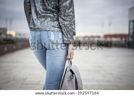 Outfit details of fashionable woman buttocks wearing jeans and sequins blazer - stock photo