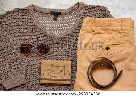 Outfit of casual woman. Brown sweater and a yellow scarf leather wallet belt shorts on a wooden background.