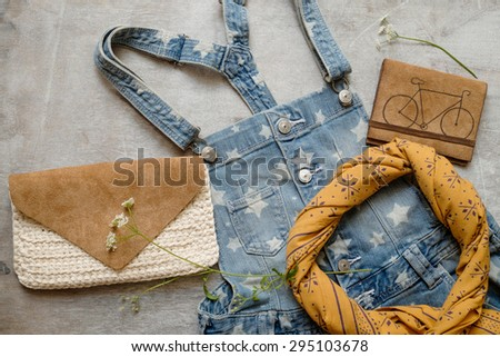 Outfit of casual woman. Denim overall with a summer female leathern bag yellow scarf on a wooden background
