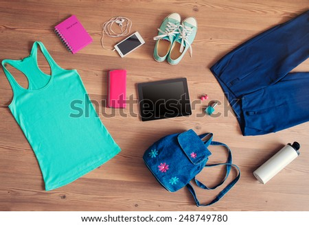Outfit of student, teenager, young woman. Overhead of essentials for modern young lady. Female clothes and accessories on wooden floor: gumshoes, pants, smartphone, bag, top, thermos, wallet, digital tablet. - stock photo