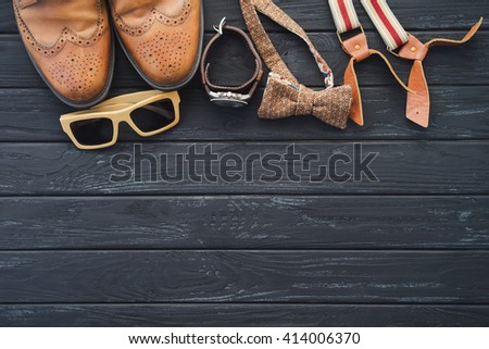 Outfit of traveler, student, teenager, hipster. Top view of essentials for modern young person. Sunglasses, bow tie, leather shoes, watch, suspenders on black wooden background - stock photo