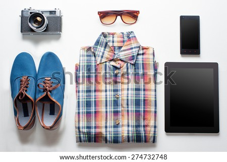 Outfit of traveler, student, teenager. Overhead of essentials for modern young person. Different objects on white wooden background. - stock photo