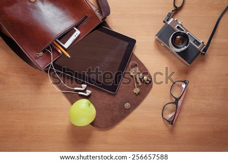Outfit of traveler, student, teenager, young man. Overhead of essentials for modern young person. Different objects on wooden background: leather bag, camera, smartphone, glasses, keys, digital tablet - stock photo