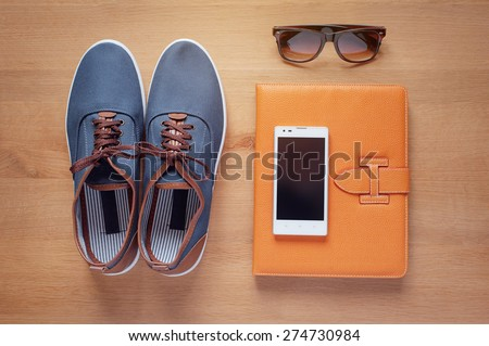 Outfit of traveler, student, teenager, young man. Overhead of essentials for modern young person. Different objects on wooden background including smart phone, sunglasses, digital tablet, gumshoes - stock photo