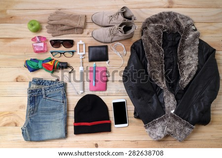 Outfit of traveler, student, teenager, young woman or guy. Overhead of essentials for modern young person. Different objects on wooden background. - stock photo