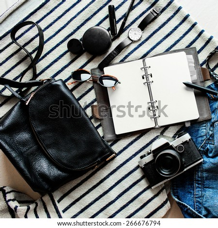 Outfit of young stylish  woman. Essentials for modern young lady. Jeans, note book, sweatshirt, nail polish, lipstick, lip pencil, powder, glasses, pen, belt, leather bag.