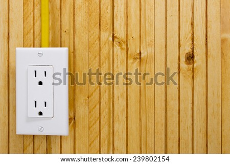 Outlet on a wooden wall with yellow cable connection. - stock photo