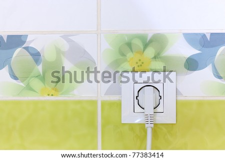 Outlet on green and white wall in bathroom - stock photo