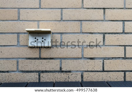 Outlet white Brown on the wall beside the pool.