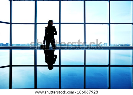 Outline of office worker with briefcase standing by the window - stock photo