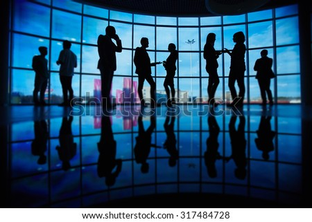 Outlines of business people communicating at meeting against window - stock photo