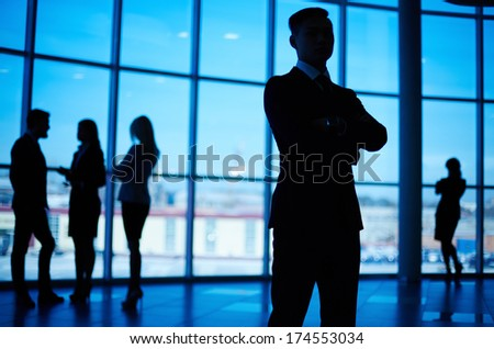 Outlines of business team standing against window with leader in front - stock photo