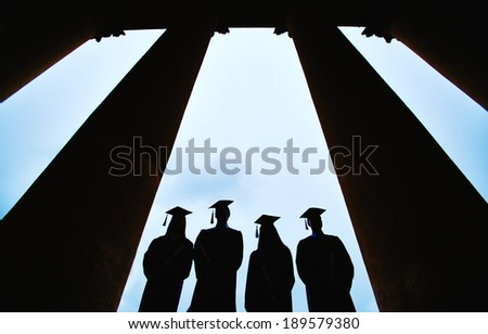 Outlines of four graduates between columns of university building - stock photo