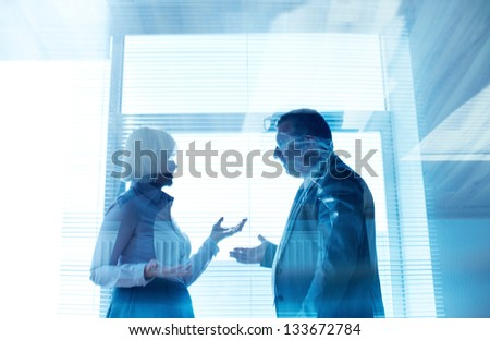 Outlines of mature businessman and his colleague communicating by the window in office - stock photo