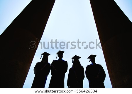 Outlines of students in graduation gowns against sky - stock photo