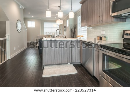 Outlook at the luxury modern kitchen with the living room at the back in a brand new house. Interior design. - stock photo