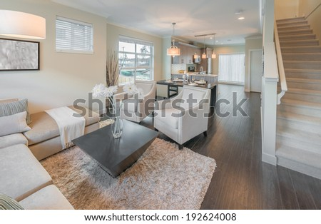 Outlook at the luxury modern living suite : family room  with two chairs  and the kitchen at the back. Interior design of a brand new house. - stock photo