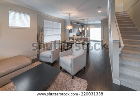 Outlook at the luxury modern living suite : family room  with two chairs  and the kitchen at the back. Interior design of a brand new house. Vertical. - stock photo